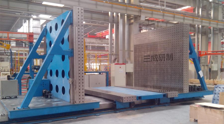 节臂桁架是履带式起重机的重要组成部分,中国现在最大的起重吨位是4200吨,从起重50吨到4200吨之间共有十几种规格;由于市场的需要,吊车的臂长各不相同,于是每种规格的吊臂增节臂通常有3、6、9和12米四种规格,加上上下节臂的数量,一般生产厂家的节臂品种多达几十种甚至上百种。虽然尺寸规格多,但其外形完全类似,企业在节臂桁架生产过程中如每个规格去做一套相应的焊接定位工装,那可想象这笔工艺装备的投资是多么庞大;如果有了这套工装,那可省去一大笔工装成本投资,包括工装场地占用成本。现该工装已经在三一、徐工、柳工、